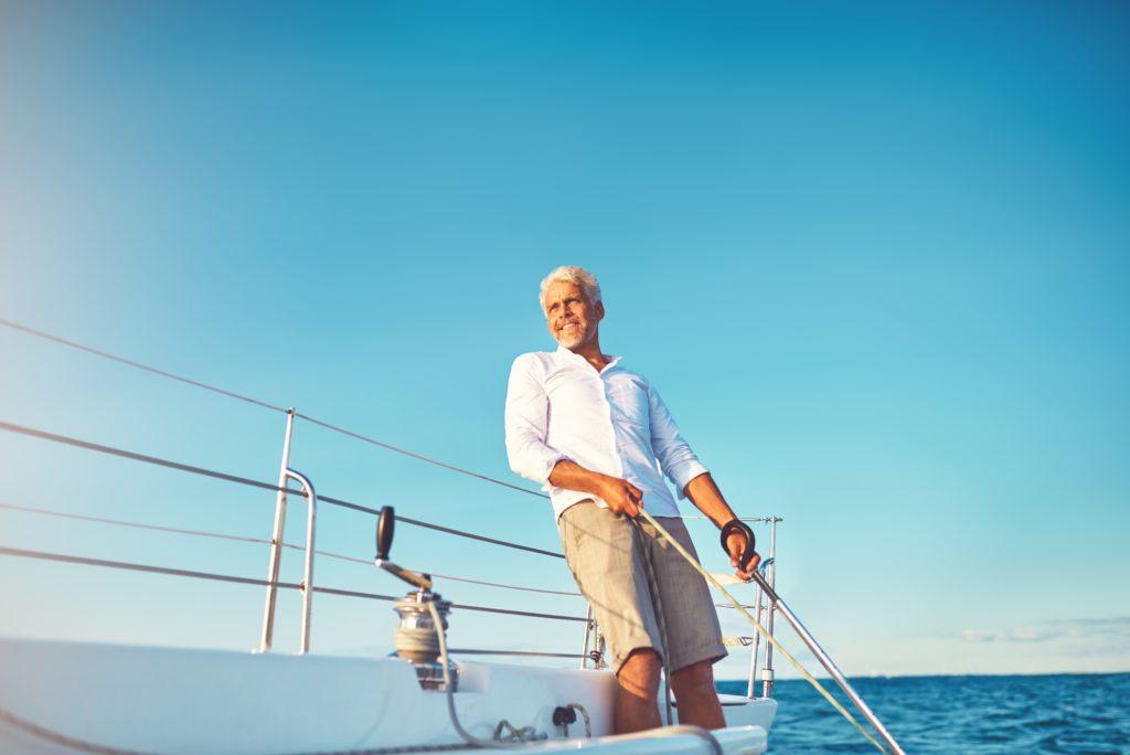 Smiling mature man enjoying a day sailing on the ocean